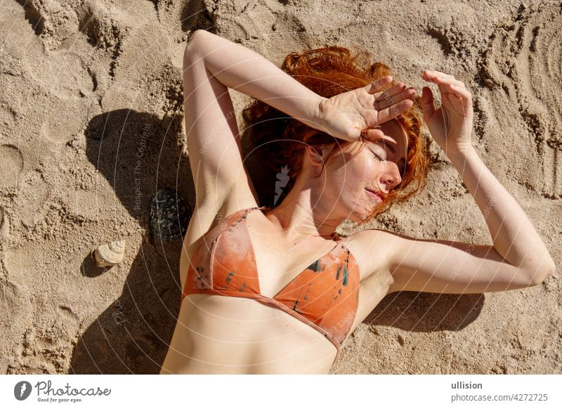 Overhead-Schuss von einem sexy Rothaarige Bikini Frau Rothaarige liegen in der Sonne auf dem Sand am Strand Rotschopf Porträt Haut außerhalb blass verführerisch
