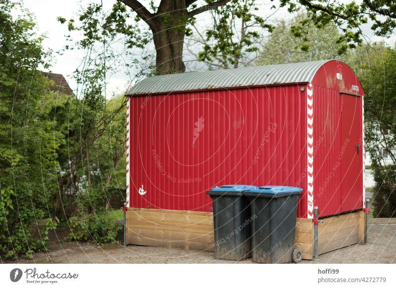 roter Bauwagen vor Baum mit zwei Altpapiertonnen auf einem Schulhof bauwagenszene Baustelle Anhänger Stilleben urban Wohnwagen Geräteschuppen