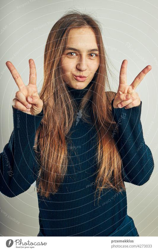 Aufgeregtes Mädchen gestikuliert Friedenszeichen. Porträt in positiver Stimmung. Mädchen macht Sieg Zeichen Geste Kopfschuss Frau Model Person jung Teenager