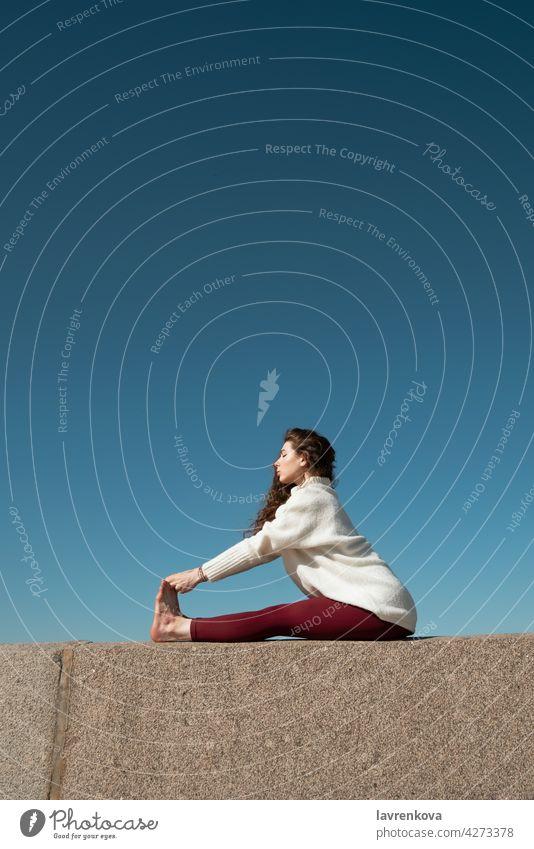 Junge brünette Frau übt Paschimottanasana Pose auf der Oberseite der Betonmauer an einem Strand vor blauem Himmel sitzende Vorwärtsbeuge paschimottanasana Yoga