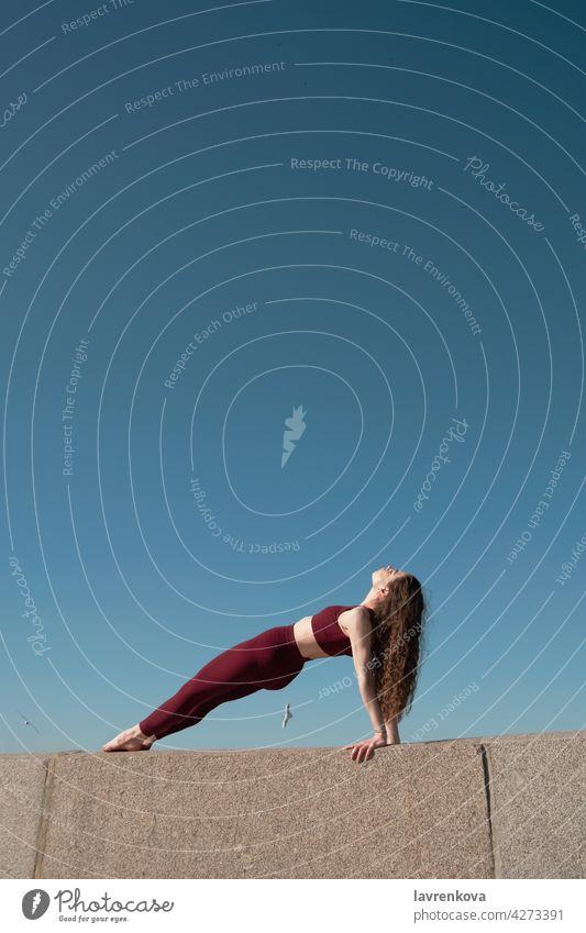 Junge brünette Frau übt Purvottanasana Pose auf der Oberseite der Betonmauer an einem Strand vor blauem Himmel Umgekehrte Plank-Pose Yoga yogini Asana Sport