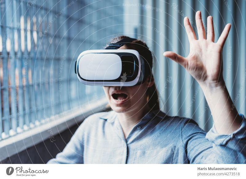frau mit vr-brille und gesichtsausdruck genießt virtual-reality-erfahrung 3d Erwachsener Hintergrund lässig Kaukasier Großstadt Kreativität cyber Gerät digital