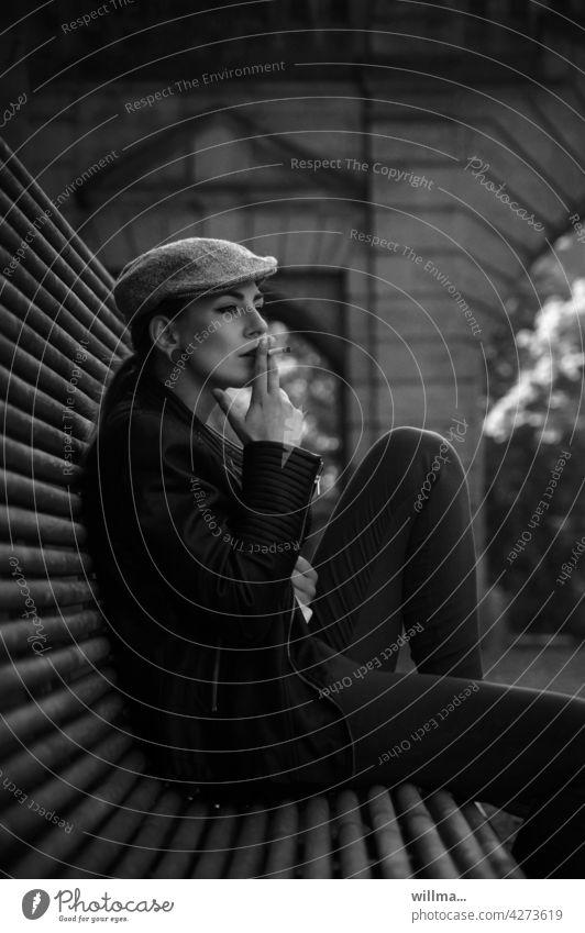 Maxi junge Frau sitzen lässig rauchen Bank Lederjacke Schiebermütze Schirmmütze 18-30 Jahre hübsch attraktiv sw Person dunkelhaarig brünett Single Schönheit