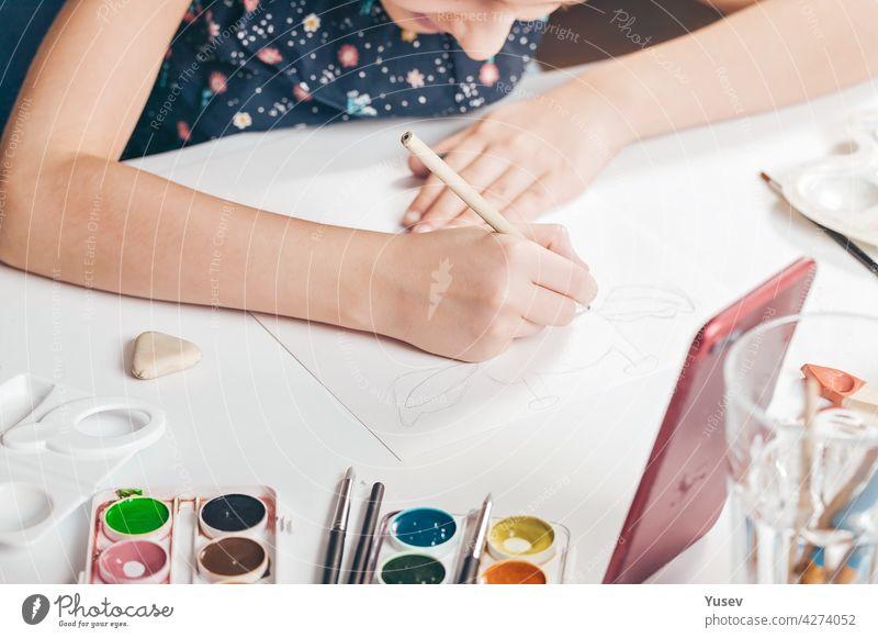 Die Hände eines niedlichen kaukasischen Mädchens zeichnen eine Bleistiftskizze. Ein Mädchen beobachtet eine Online-Lektion auf einem Smartphone. Unterricht mit Kindern zu Hause. Hände im Rahmen