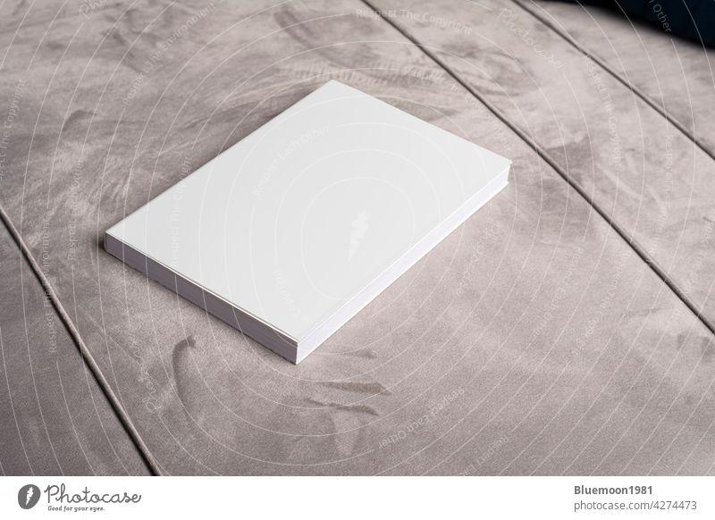 Buch mit leerem Einband auf grauem Samt-Sofa-Hintergrund Attrappe editierbar Wandel & Veränderung blanko Vorlage realistisch schwarz Taschenbuch Werbung