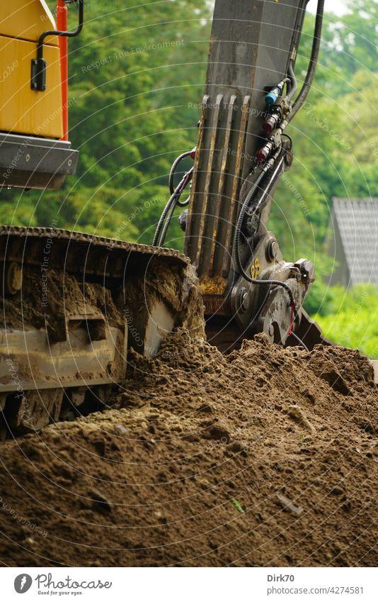 Detail eines Baggers auf einem Erdhaufen Baustelle Bauindustrie Schaufel Baggerschaufel Erde aushub ausheben baggern Kette Raupenkette Detailaufnahme Industrie