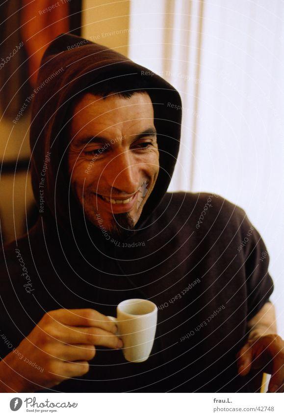 kein Mönch trinken Espresso Tasse Freude Gesicht Mann Erwachsene Bart Hand T-Shirt lachen Fröhlichkeit Optimismus Kapuze Café Porträt