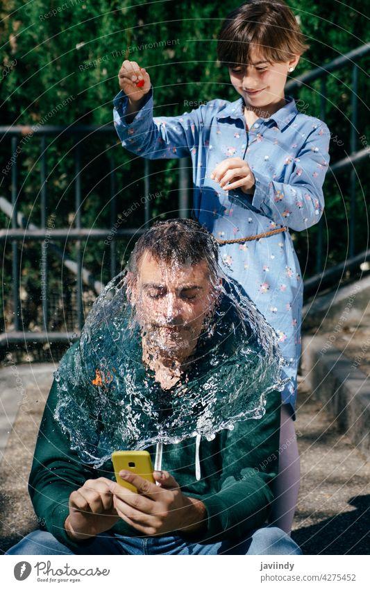 Mädchen bläst einen mit Wasser gefüllten Ballon über dem Kopf ihres Vaters auf Luftballon geplatzt platschen Tochter nass Pop Spray Aktion Einschlag Hintergrund