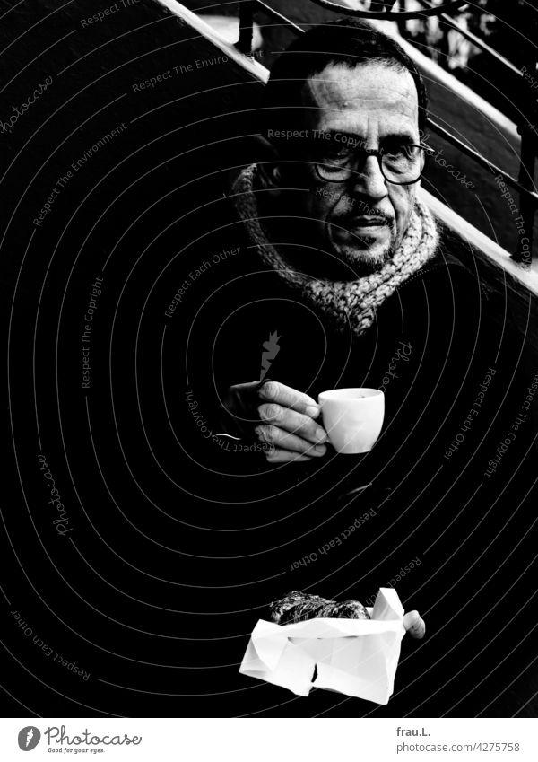 Coronacafe ernsthaft Porträt Gesicht Mann Brille Winter Jacke sitzen kalt Pandemie Schal Espresso Handschuhe Croissant Serviette Bank Sitzbank Treppe