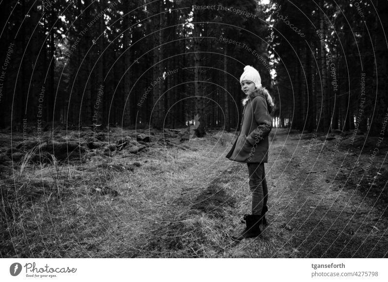 Winterspaziergang im Wald Kind Mütze kalt Spaziergang Spaziergang in der Natur Schwarzweißfoto Waldweg Außenaufnahme Bäume Mantel wandern Baum Erholung