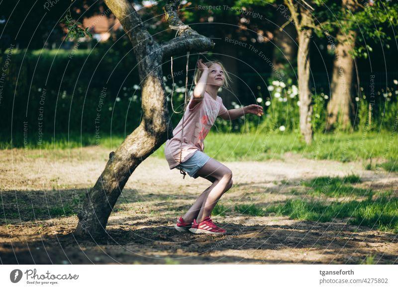 Kind spielt mit einem Seil an einem Apfelbaum im Garten spielen Baum Farbfoto Außenaufnahme klettern schaukeln Freude Sommer Fröhlichkeit Natur Spielen Kindheit