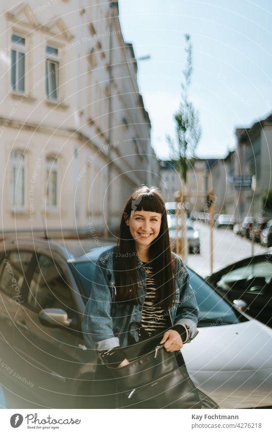 junge Frau lächelt in die Kamera Erwachsener attraktiv schön sorgenfrei Autos lässig Kaukasier heiter schick niedlich Jeansstoff elegant Brille Weiblichkeit