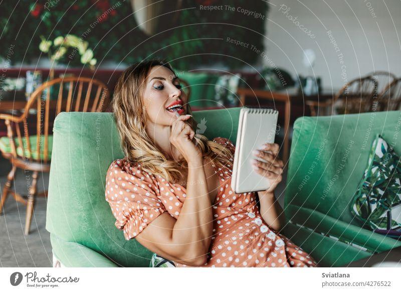 Eine junge Frau sitzt auf einem Stuhl an einem Tisch in einem Café, hält einen Stift in den Händen und schaut nachdenklich in ihr Notizbuch Notebook Kaffee