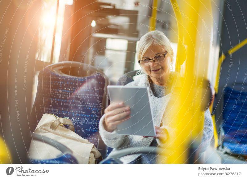 Ältere Frau benutzt Tablet, während sie mit dem öffentlichen Bus fährt Senior Senioren Rentnerin Rentnerinnen lässig im Freien eine Person