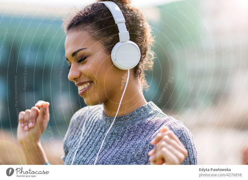 Glückliche junge Frau hört Musik in Kopfhörer in der Stadt im Freien Tag Positivität selbstbewusst sorgenfrei Menschen junger Erwachsener lässig schön attraktiv
