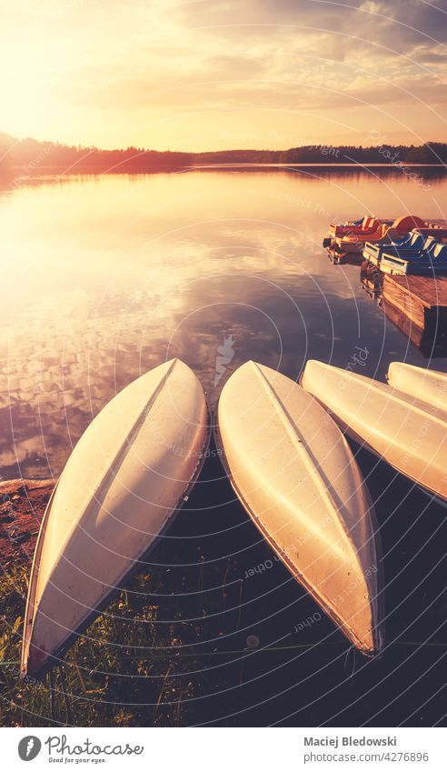 Kajaks an einem See bei Sonnenuntergang, Farbtonung aufgetragen. Wasser Sommer Kanu Natur Erholung Freizeit Sport Aktivität Pier im Freien niemand Abend Urlaub