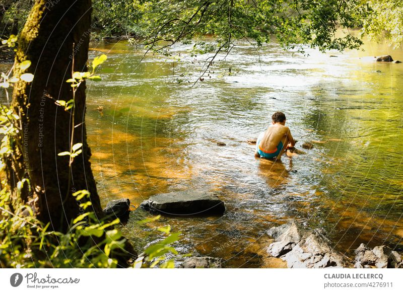 Junger Junge sitzt und spielt im Fluss Rückansicht kleiner Junge sitzend Sitzen jung Lifestyle männlich Person Kind Menschen niedlich Porträt Bildung Spielen