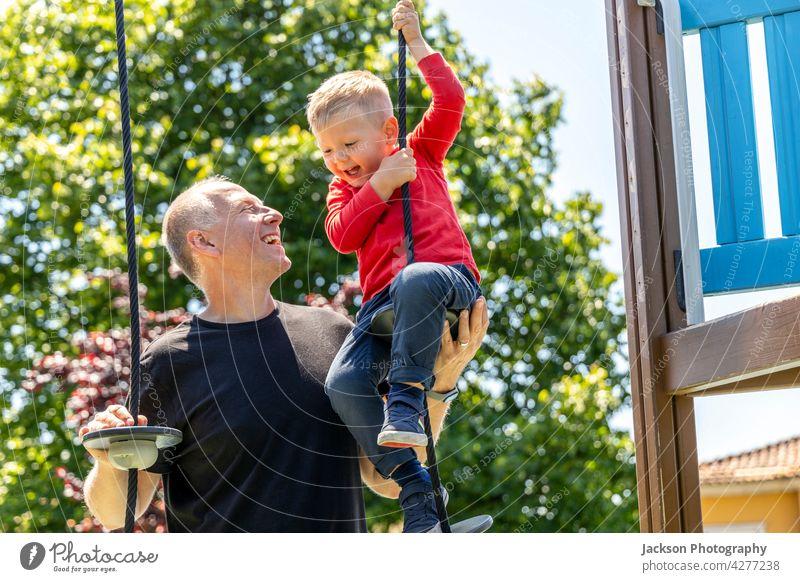 Vater spielt mit seinem 3 Jahre alten Sohn auf dem Spielplatz Spaß Kind Kleinkind Kinder Porträt Natur Lachen Bonden Zusammengehörigkeitsgefühl Elternschaft