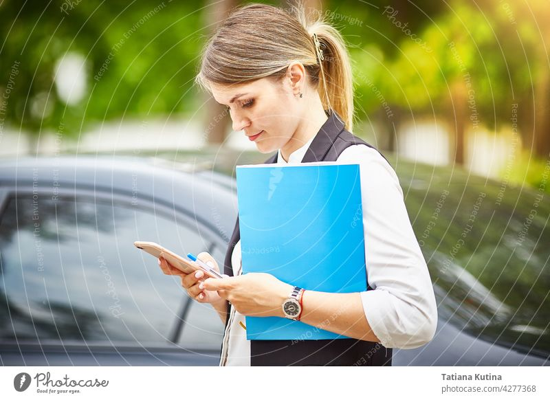 Eine junge Geschäftsfrau mit einer Mappe für Papiere in den Händen schaut auf ihr Smartphone Texten Manager Telefon Person beschäftigt professionell Büro Frau