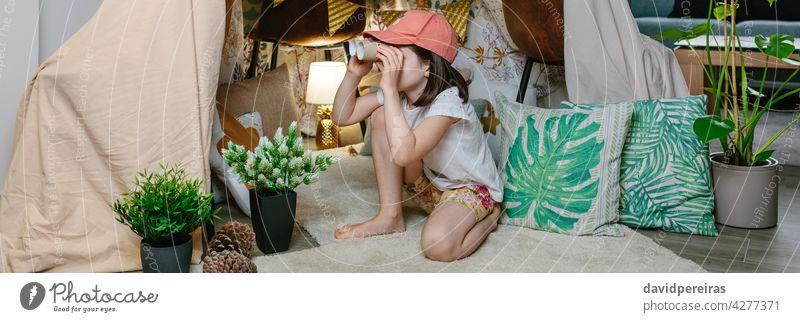 Mädchen spielt mit Karton Fernglas beim Camping zu Hause beobachtend spielen heimwärts diy Zelt staycation Toilettenpapierhülsen Schachtel Transparente Netz