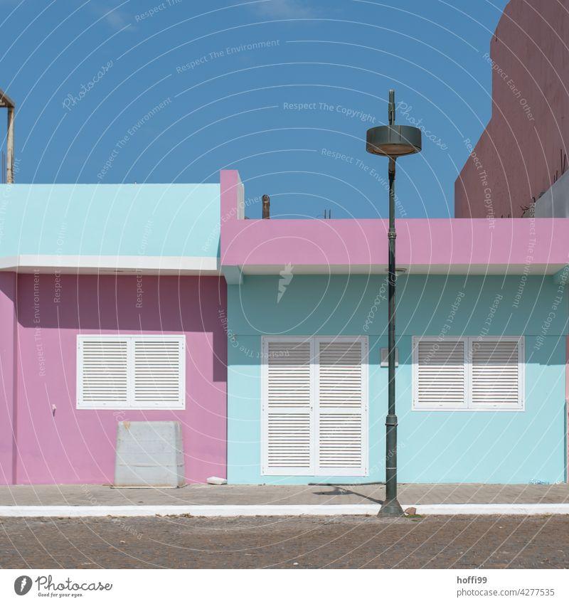 türkis, pink, weiß, blau - Häuserfassade mit Strassenbeleuchtung und wolkenlosem Himmel bunt Fassade Laterne Straßenbeleuchtung Sonnenlicht hell Mittagspause