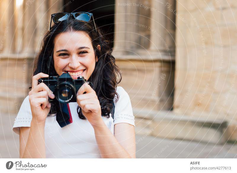 Glückliche Touristin, die mit einer Retro-Kamera Bilder von der Altstadt macht Frau jung Lächeln zahnfarben Fotokamera Fotografie retro Sommer Mädchen Menschen
