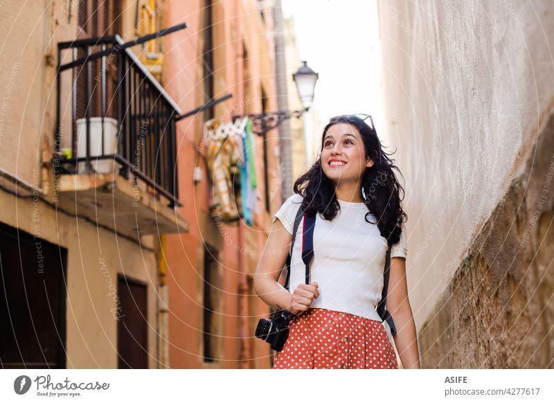 Junge glückliche Tourist Frau zu Fuß nach unten eine europäische Stadt Gasse mit einer Kamera reisen Urlaub Mädchen Feiertag Großstadt Glück Fahrspur Backstreet