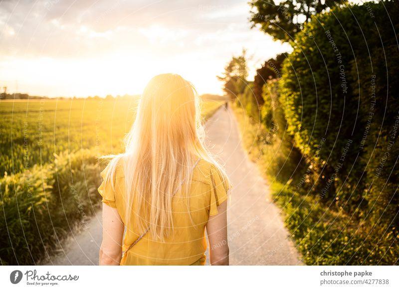 Rückansicht blonde frau spaziergang abends auf feld, tiefstehende Sonne Frau Spaziergang Feld Abend feldweg Abendlicht Sommer Haare Gegenlicht spazieren gehen
