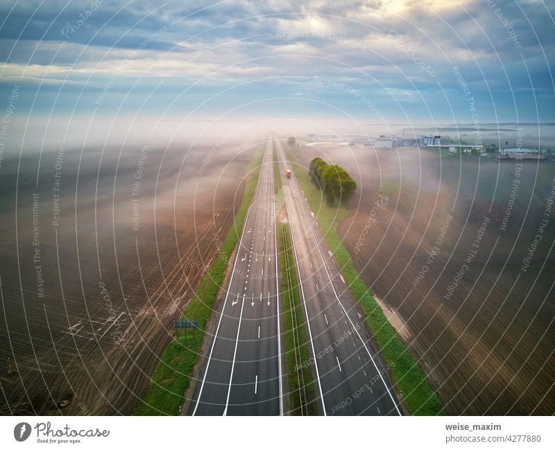 Luftaufnahme einer von Nebel bedeckten Autobahn. Früher nebliger Morgen. Straße im regnerischen Frühling Sommer Felder. Cloud Regen Wetter Verkehr ländlich