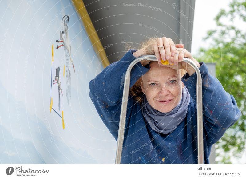 Frau, Malerin, Künstlerin in den Vierzigern oder Fünfzigern mit Sommersprossen und roten Haaren steht auf einer Leiter mit einem kleinen Pinsel in der Hand, Kopierraum