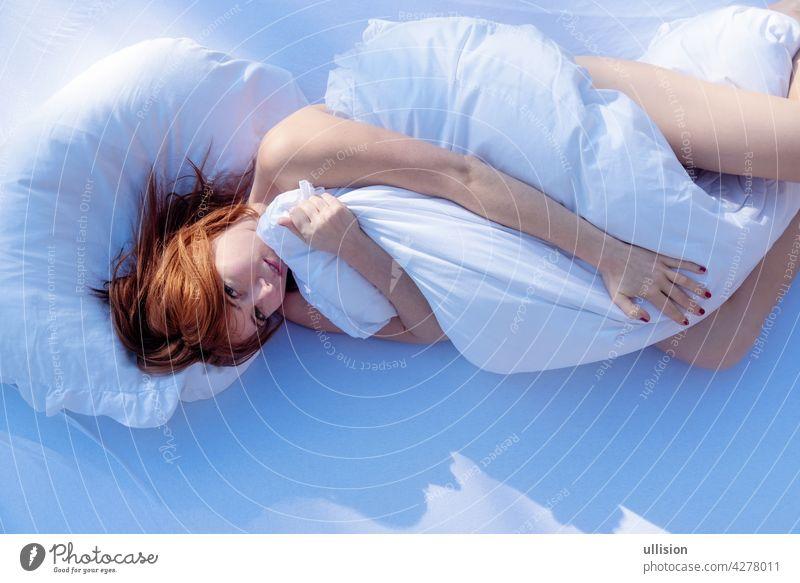 Blick von oben auf eine attraktive, junge, sexy, rothaarige, Frau im Sonnenlicht kuschelt im Bett und umarmt die weiche Bettdecke im Schlafzimmer, Kopie Raum.