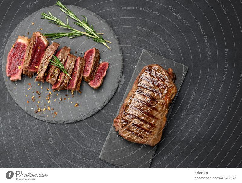 gebratene, in Stücke geschnittene Rindersteaks auf einem schwarzen Brett, Garheitsgrad blutig oben Transparente Barbecue grillen Rindfleisch Beefsteak