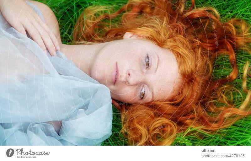 Porträt einer schönen jungen sexy rothaarigen Frau, die glücklich in der Frühlingssonne liegt und sich im Gras entspannt, die roten Haare frei um den Kopf drapiert.