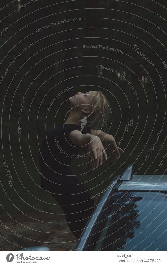 Ein blondes Mädchen in schwarzer Kleidung hält das Gleichgewicht, lehnt sich aus dem Fenster des Autos, in einer eleganten Pose mit ausgestreckten Armen und zurückgeworfenem Kopf vor dem Hintergrund eines sommerlichen Dämmerwaldes.