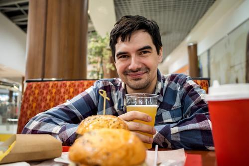Mann isst Fastfood-Burger und trinkt Bier allein im offenen Bereich eines Restaurants in einem Einkaufszentrum Mahlzeit Lebensmittel Bar Glück Pub essen schnell