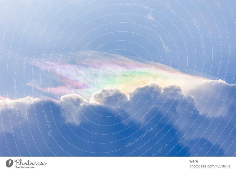 Federwolken in zarten Regenbogenfarben am Rande einer Kumulus-Gewitterwolke Tropfen Regentropfen Wolkenformation filigran Lichtschein Hagel mächtig