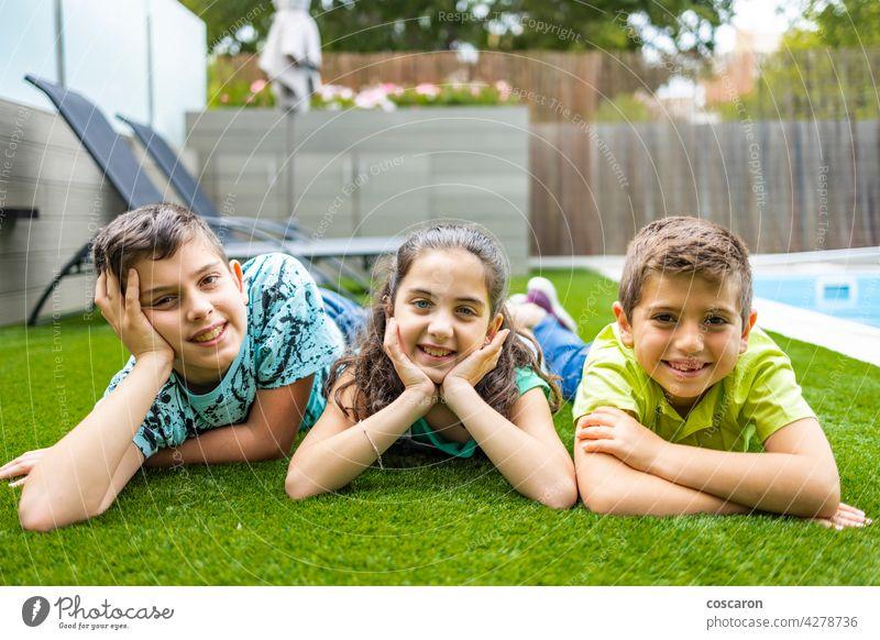 Porträt von drei Kindern auf einem Gras liegend Hintergrund schön Junge lässig Kaukasier heiter Kindheit genießen Familie Feld Freunde Freundschaft Spaß Mädchen
