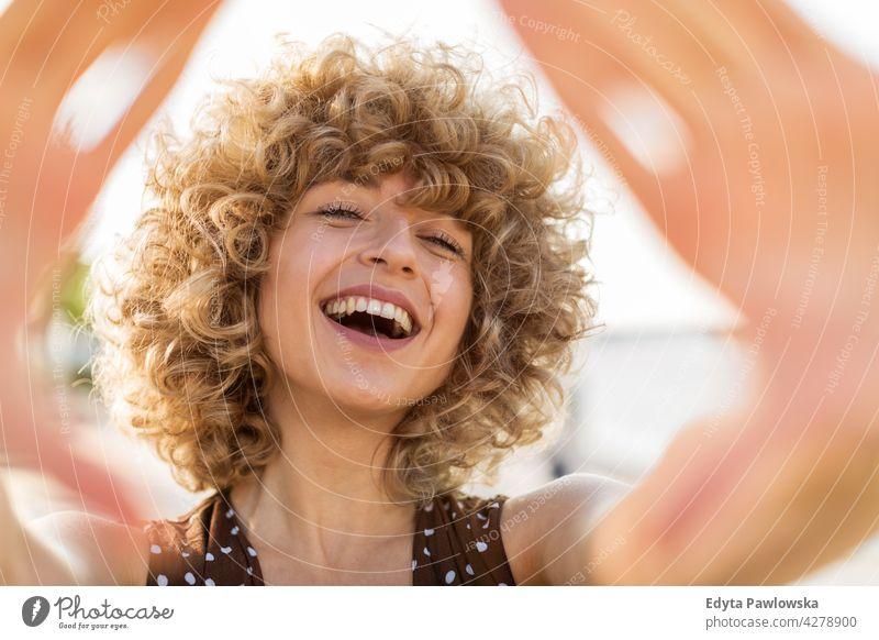 Porträt der jungen Frau mit lockigem Haar lächelnd Jahrtausende urban Straße Großstadt stylisch Menschen junger Erwachsener lässig attraktiv Lächeln Glück