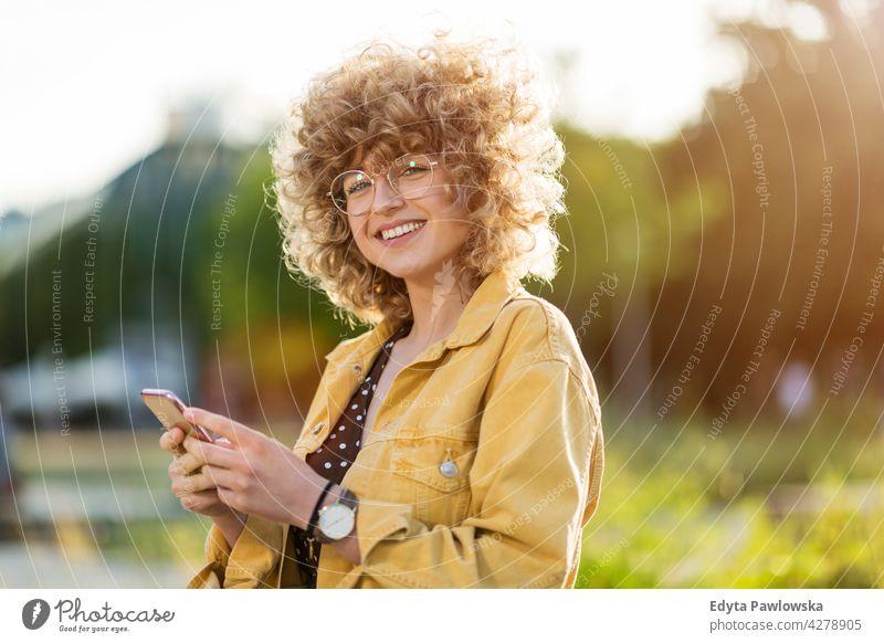 Junge Frau mit Mobiltelefon in der Stadt Jahrtausende urban Straße Großstadt stylisch Menschen junger Erwachsener lässig attraktiv Lächeln Glück Kaukasier