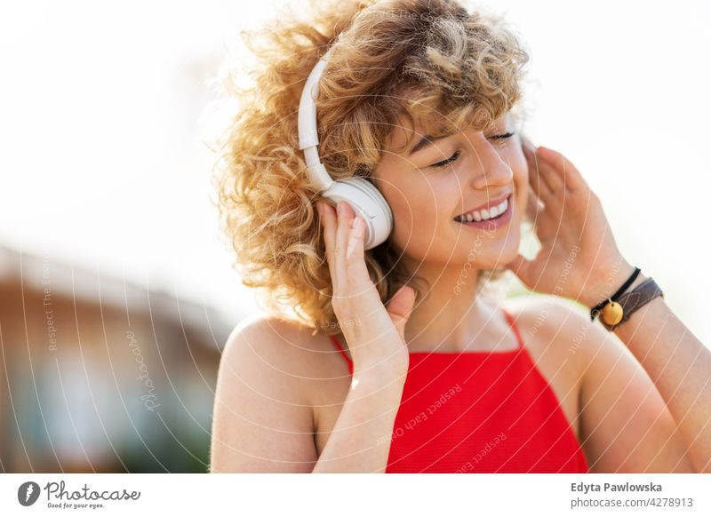 Porträt einer jungen Frau mit Kopfhörer Jahrtausende urban Straße Großstadt stylisch Menschen junger Erwachsener lässig attraktiv Lächeln Glück Kaukasier