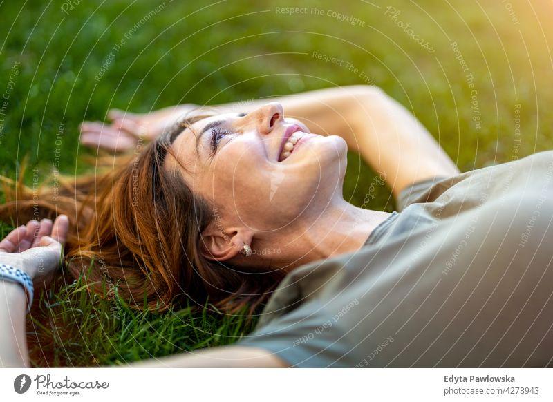 Sorglose Frau auf dem Gras in der Sonne liegend hoher Winkel Tagträumen oben träumend ruhen grün Lügen Rasen Wiese Park Natur Frühling rote Haare Rotschopf