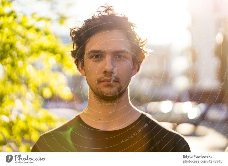 Porträt eines gutaussehenden jungen Mannes in der Stadt sonnig außerhalb lockig Behaarung Hipster Person Erwachsener Selbstvertrauen im Freien Sommer männlich