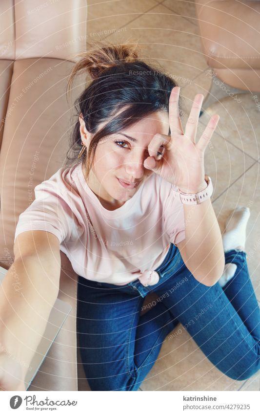 Junge Frauen sitzen auf dem Boden und nehmen Selfie, während OK Fingerzeichen zeigen jung Gesten Vorzeichen Lächeln anhaben Attrappe T-Shirt Draufsicht Hand