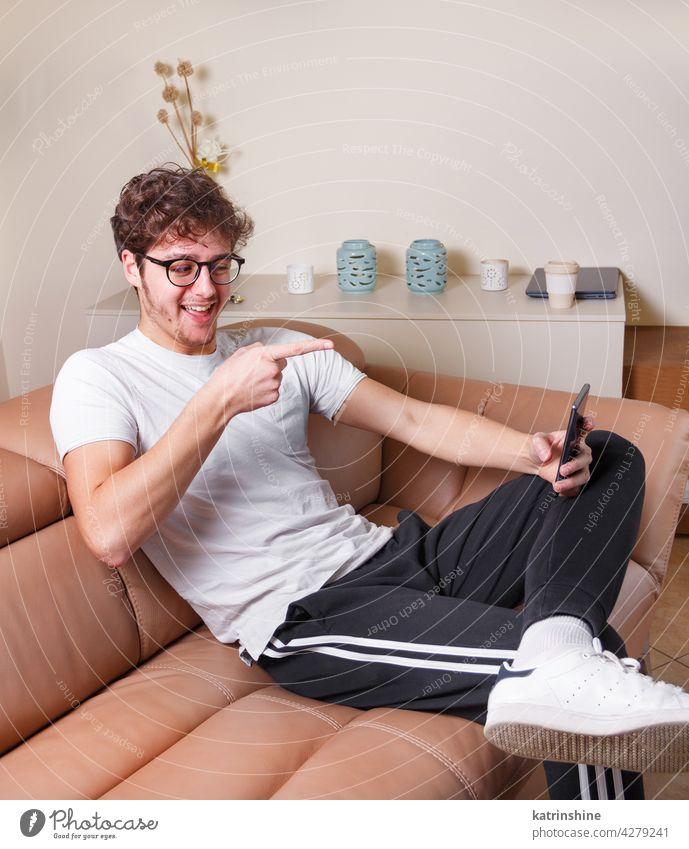Junge Männer machen Videoanruf mit Telefon beim Sitzen auf dem Sofa zu Hause jung Punkt Attrappe T-Shirt Smartphone Handy Lifestyle Jeanshose anhaben allein