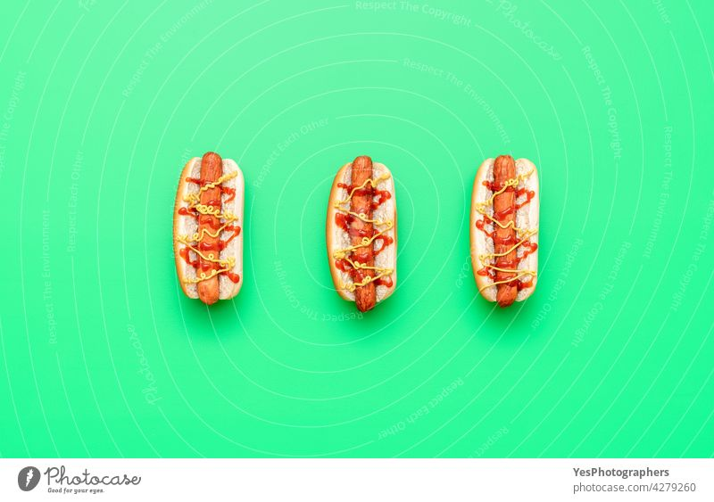 Hot Dogs Draufsicht minimalistisch auf einem grünen Tisch oben Amerikaner Hintergrund Brot Brötchen Kalorien Farbe Textfreiraum Küche ausschneiden lecker essen