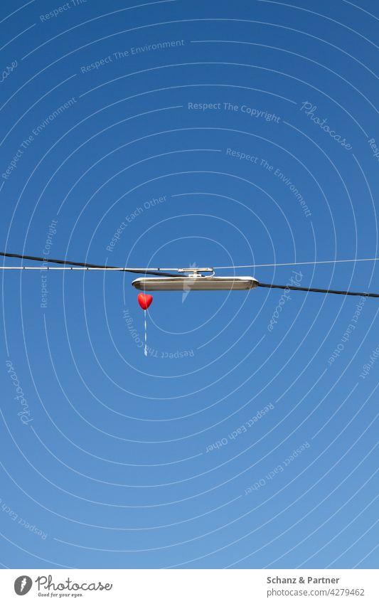 roter Herzballon fliegt in den Himmel fliegen Liebe heiraten Hochzeit Lustballon Hindernis Straßenbeleuchtung Stromleitung Tradition wegfliegen Romantik Gefühle