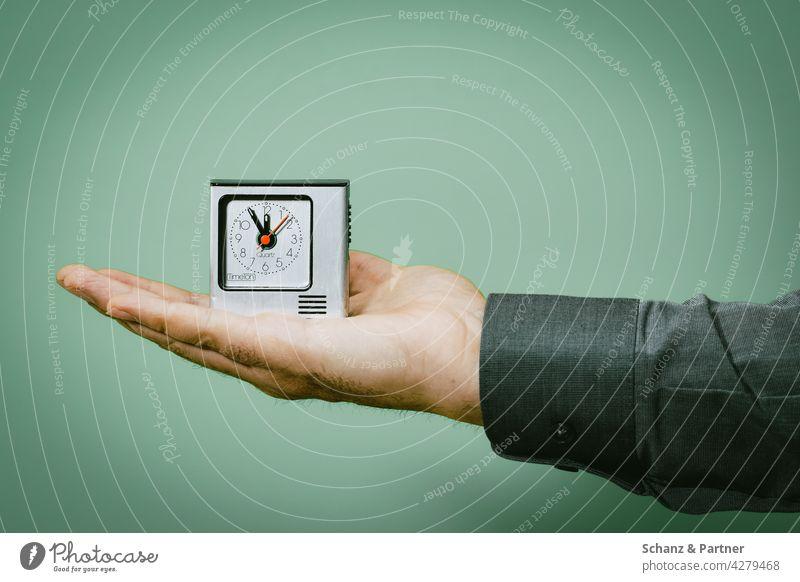 Wecker auf der Handfläche Zeitmanagement fünf vor zwölf Uhr Uhrzeit Eile eilig Zeiterfassung Zeitplanung halten farbiger Hintergrund Freisteller freigestellt