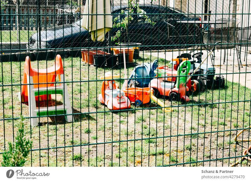 bunte Spielfahrzeuge im Garten Spielsachen Plastik Zaun Fuhrpark Fahrzeuge spielen Lockdown Privatsphäre Wiese Gras Rasen Außenaufnahme Spielen Kontaktsperre