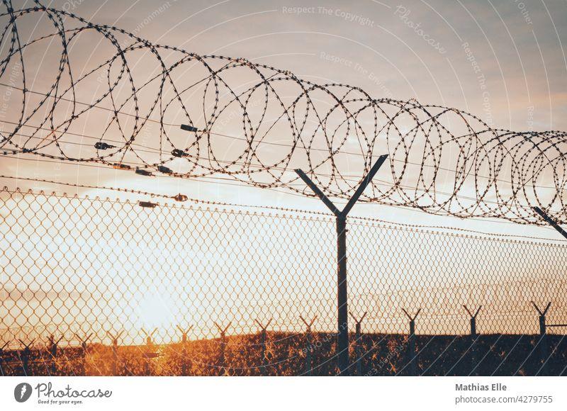 Maschendrahtzaun mit Stacheldraht Zaun Stacheldrahtzaun bedrohlich Sicherheit gefährlich Barriere Grenze Verbote Himmel blau Justizvollzugsanstalt gefangen