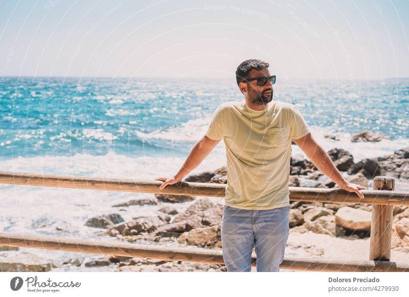 Mann genießt einen sonnigen Tag an der Küste Erwachsener attraktiv Strand Vollbart blau Boote Junge brünett Kaukasier niedlich genießend Genuss Gesicht Spaß Typ